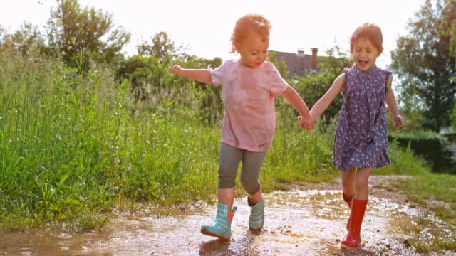 slo mo två små flickor hålla händerna som de kör över en lerig pöl i sina regn stövlar - lera jord bildbanksvideor och videomaterial från bakom kulisserna