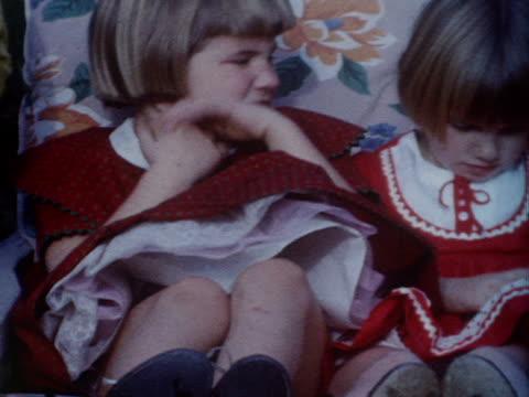 vidéos et rushes de two little girls in red dresses sit and pout. - soeur
