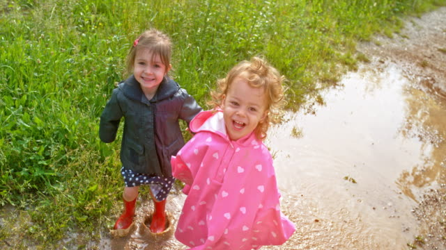slo mo two little girls jumping in a muddy puddle and smiling into the camera - children only video stock e b–roll