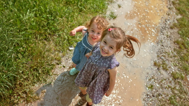 slo mo two little girls laughing into the camera while jumping in the muddy puddle - mud stock videos & royalty-free footage