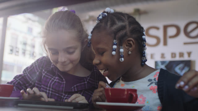 ms. two little girls look at tablet computer and laugh in coffee shop. - treccine video stock e b–roll