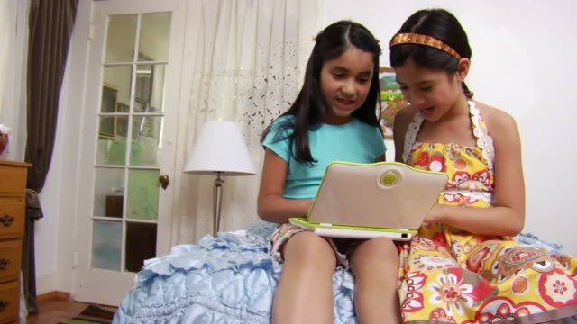 MS Two little girls playing on laptop at home / Los Angeles, California, United States
