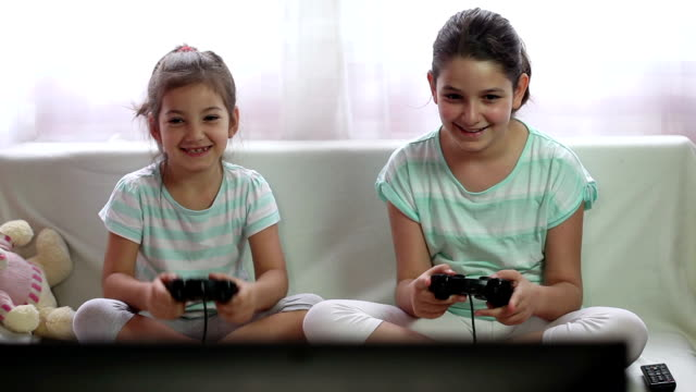 two little girls playing video games - girl cross legged stock videos & royalty-free footage