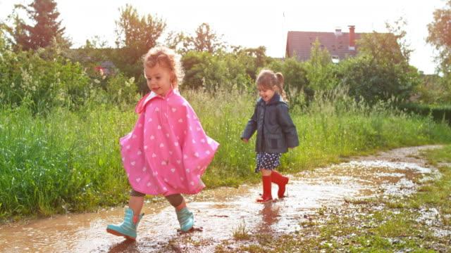 vídeos de stock, filmes e b-roll de duas meninas que atravessa uma poça de lama nos subúrbios - capa de chuva
