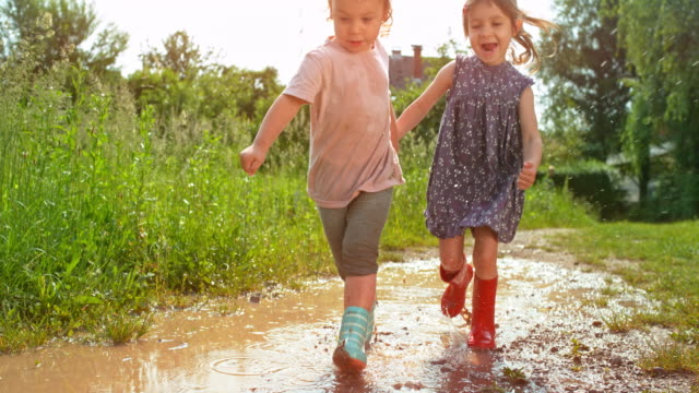 slo mo two little girls running across a muddy puddle while holding hands and laughing - maglietta video stock e b–roll