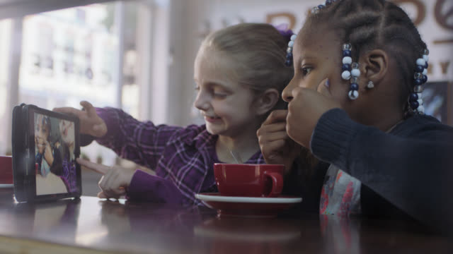 ms. two little girls take silly selfies with tablet in coffee shop. - children only stock videos & royalty-free footage