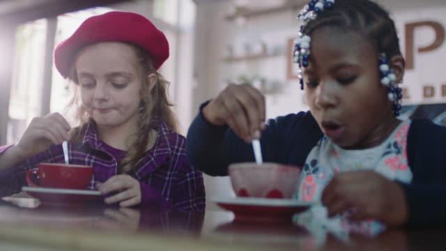 vídeos de stock, filmes e b-roll de ms. two little girls taste, stir, and accidentally spill hot chocolate in cute coffee shop. - colher faqueiro