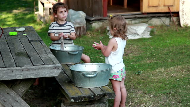 two little girls washing clothing in the backyard - adult imitation stock videos and b-roll footage