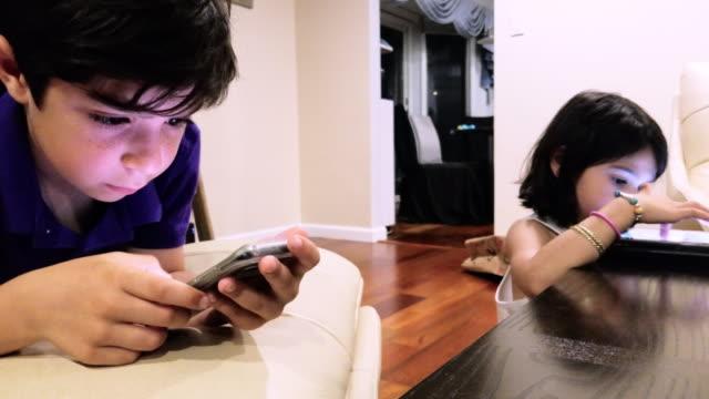 due bambini piccoli, fratello e sorella, che giocano con i gadget in salotto - divisione video stock e b–roll