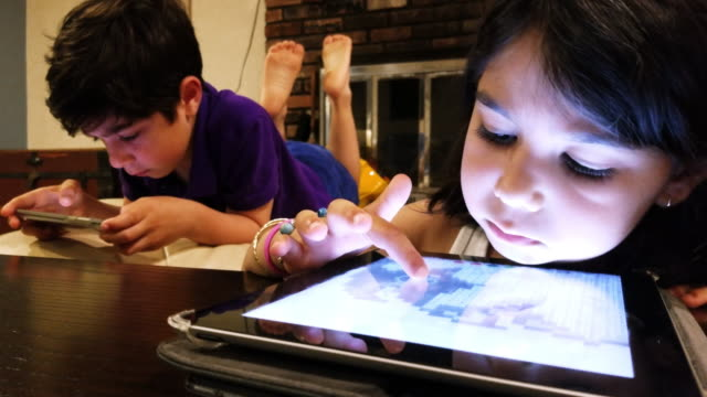 two little kids, brother and sister, playing with gadgets in the living room - boys stock videos & royalty-free footage