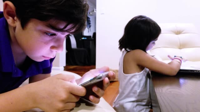 Two little kids, brother and sister, playing with gadgets in the living room