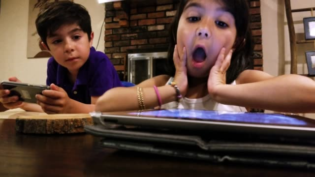 two little kids, brother and sister, playing with gadgets in the living room - microsoft stock videos and b-roll footage