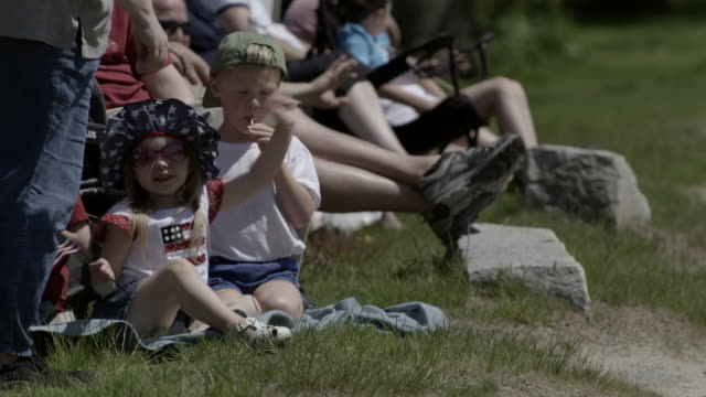 two little kids sitting on grass waving american flags and cheering as small town parade passes by. - parade stock videos & royalty-free footage