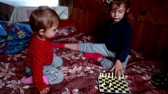 two little sisters playing with chess pieces on the bed - square composition stock videos & royalty-free footage