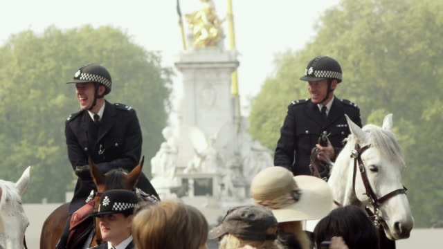ms two london mounted police officers smiling and laughing in a large crowd of people / london, united kingdom - uk video stock e b–roll