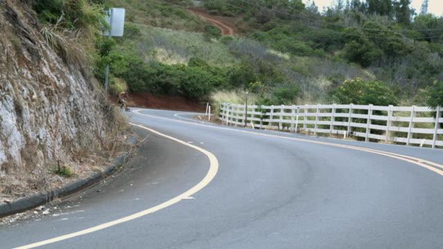 WS PAN Two long boarders riding downhill on windy coastal road / California, USA