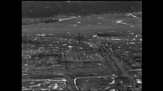 two long rows of buildings with cars in the parking lot and telephone poles in the foreground; aerial view of suburban neighborhood with patches of... - 1940 1949 video stock e b–roll