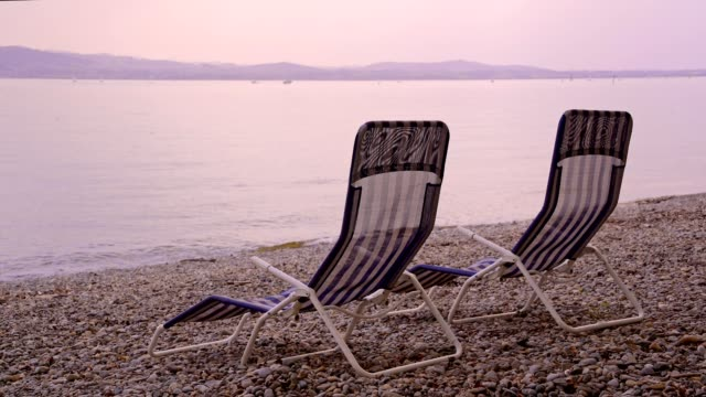 vídeos de stock e filmes b-roll de two lounge chairs on the lakeshore, kreesbronn am bodensee, lake constance, baden-württemberg, germany - dois objetos