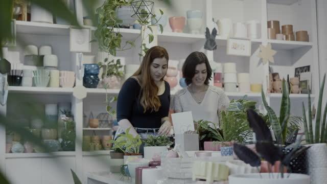 植物やギフトショップで2人の素敵な女性の顧客の買い物 - ギフトショップ点の映像素材/bロール