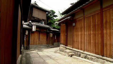 two maiko wearing summer kimonos walk through an alley. - tradition bildbanksvideor och videomaterial från bakom kulisserna