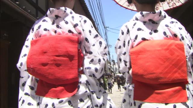 Two maiko wearing yukata carry umbrellas as they walk down a narrow street.