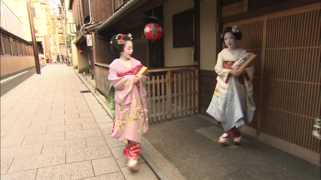 Two Maikos leave a house and walk down an alleyway.