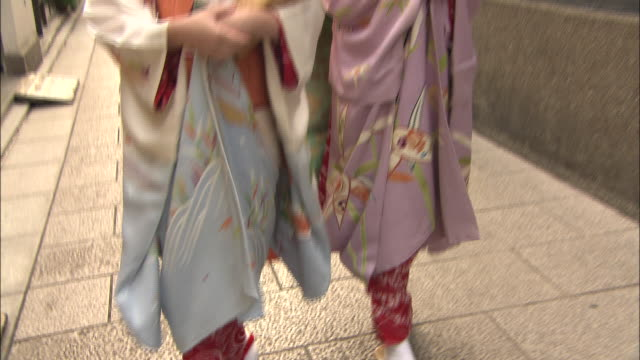 two maikos walk through an alleyway in the gion district of kyoto. - kyoto stock videos and b-roll footage