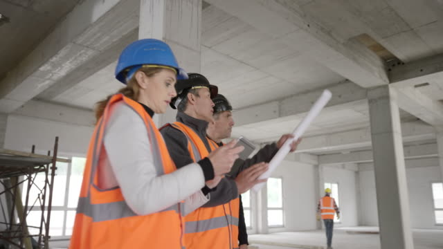 ts two male architects and a forewoman holding a digital tablet checking the progress at the busy construction site - caucasian appearance stock videos & royalty-free footage