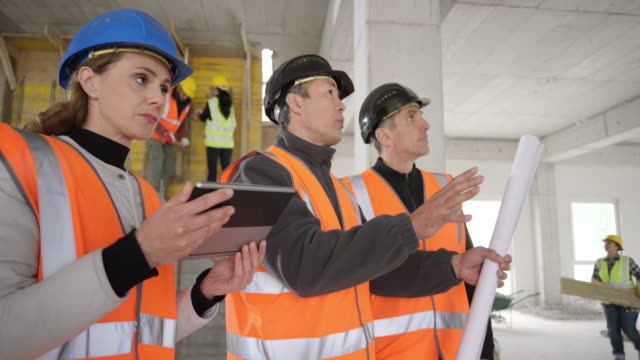 two male architects talking with the forewoman at the construction site on the ground floor of the industrial building - foreman stock videos & royalty-free footage