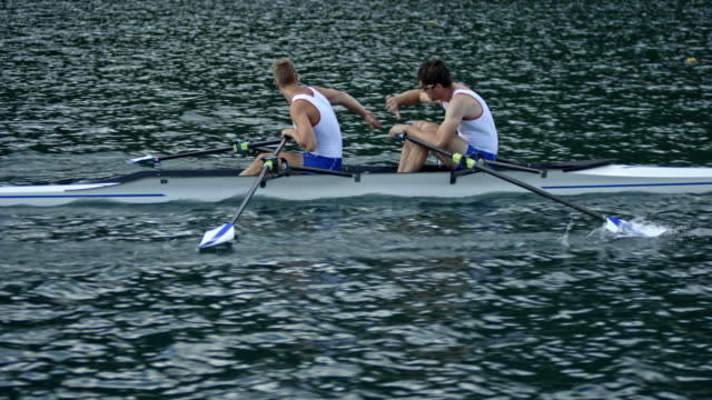 TS Two male athletes in a double scull taking a break in their training and shaking hands