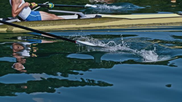 stockvideo's en b-roll-footage met slo mo twee mannelijke atleten roeien over een meer in de zon - sunshine lake