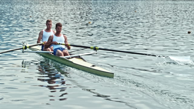 two male athletes rowing across a lake - rowing stock videos & royalty-free footage