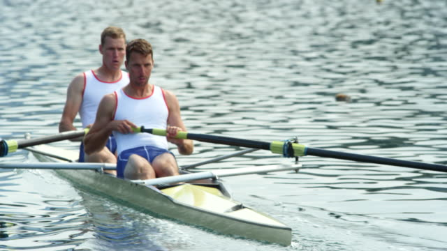 two male athletes rowing in a coxless pair across the lake - canottaggio senza timoniere video stock e b–roll