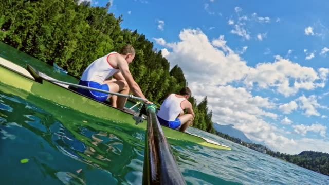 pov two male athletes rowing in a coxless pair on a sunny day - scull stock videos & royalty-free footage