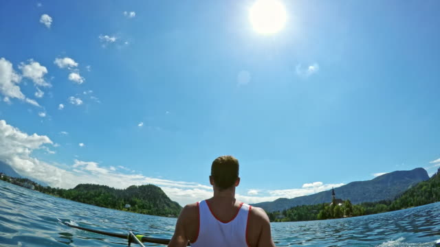 POV Two male athletes rowing on a lake in sunshine