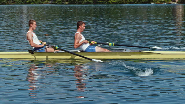 SLO MO TS Two male athletes rowing on a sunny day