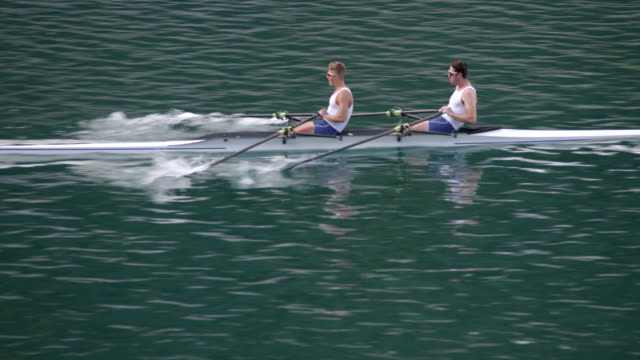 ts two male athletes sculling across a lake - sculling stock videos & royalty-free footage