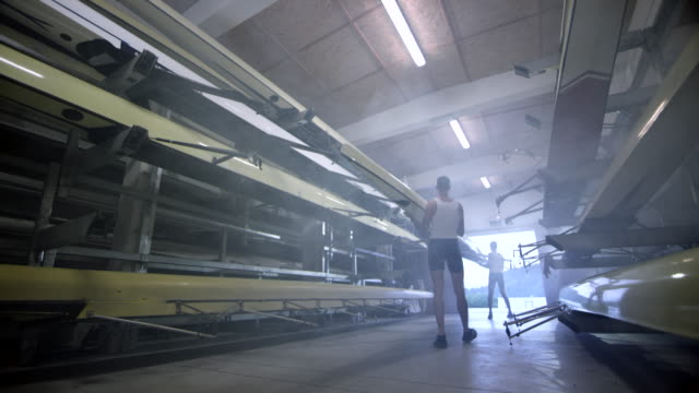 slo mo two male athletes taking a sweep oar boat out of the boathouse - scull stock videos & royalty-free footage