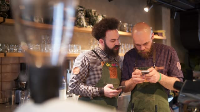 two male barista on a coffee break on the work - barba peluria del viso video stock e b–roll
