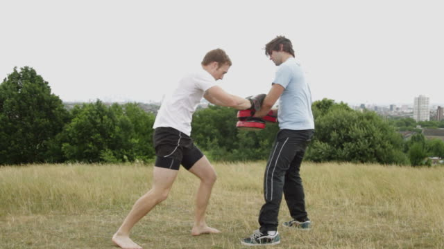 Two male box training in park