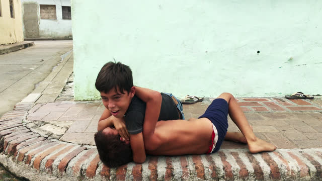 two male boys horse-play in a colonial-style sidewalk in the city on november 16, 2016; in camaguey, cuba. as computers and technology has not made... - simple living stock videos & royalty-free footage