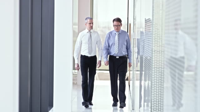 SLO MO Two male business coworkers walking down hallway and talking