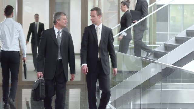 DS Two male business men talking and walking down the hallway