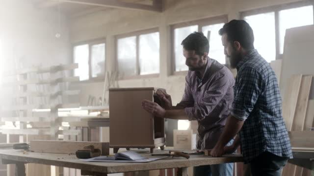 zwei männliche schreiner arbeiten gemeinsam an ein möbelstück - schreiner stock-videos und b-roll-filmmaterial