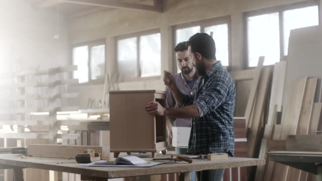 Two male carpenters working together on piece of furniture