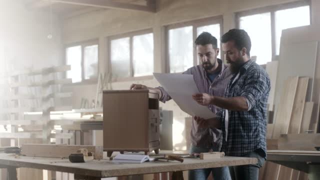 vídeos de stock, filmes e b-roll de dois carpinteiros masculinos trabalhando juntos na peça de mobiliário - pau objeto manufaturado