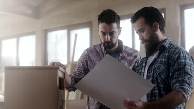 vídeos de stock, filmes e b-roll de dois carpinteiros masculinos trabalhando juntos na peça de mobiliário - male friendship