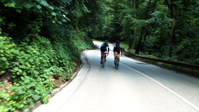 two male cyclists riding uphill on mountain roadway - sportsperson stock videos & royalty-free footage