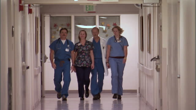 SLO MO, MS, Two male doctors and two female nurses walking down hospital hallway
