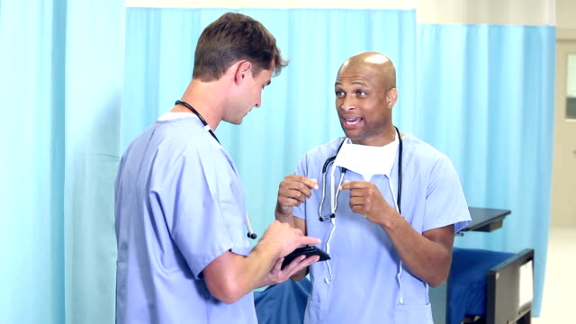 two male doctors or nurses walking in hospital, talking - nursing student stock videos and b-roll footage